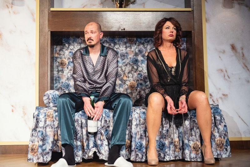 Sypialnia. Na łóżku siedzi para. Patrzą przed siebie z rezygnacją.