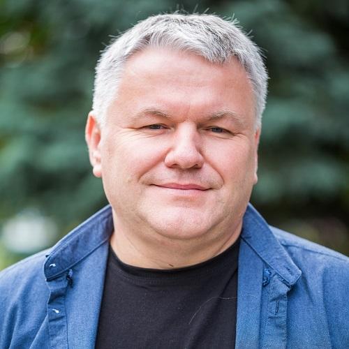 Darek Zajkowski. W tle zieleń.
