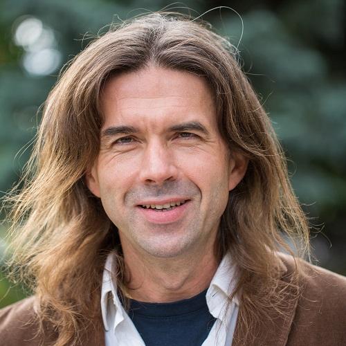 Robert Więckowski. W tle zieleń.