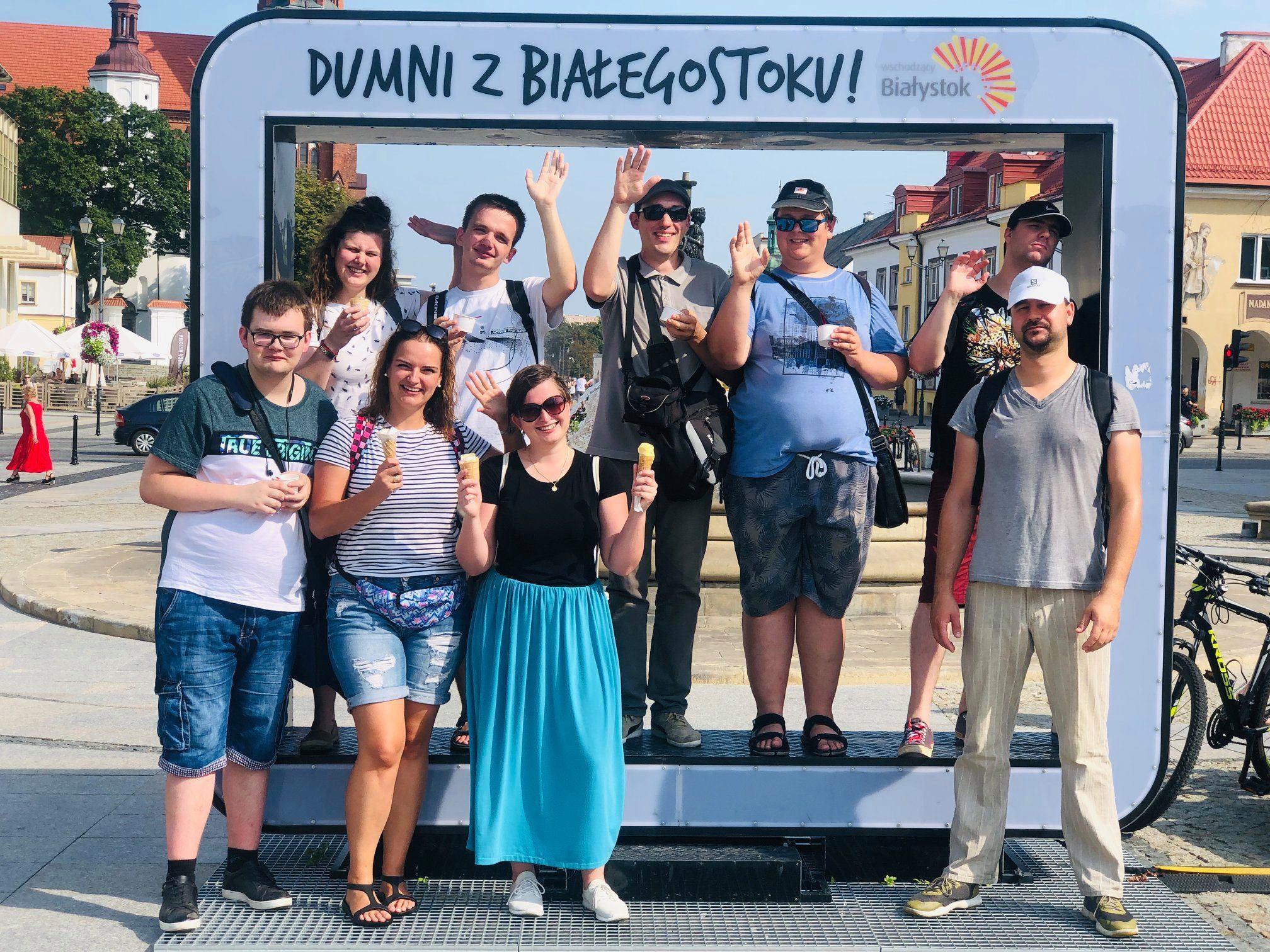 Przed ramką Dumni z Białegostoku stoją uczestnicy rajdu.