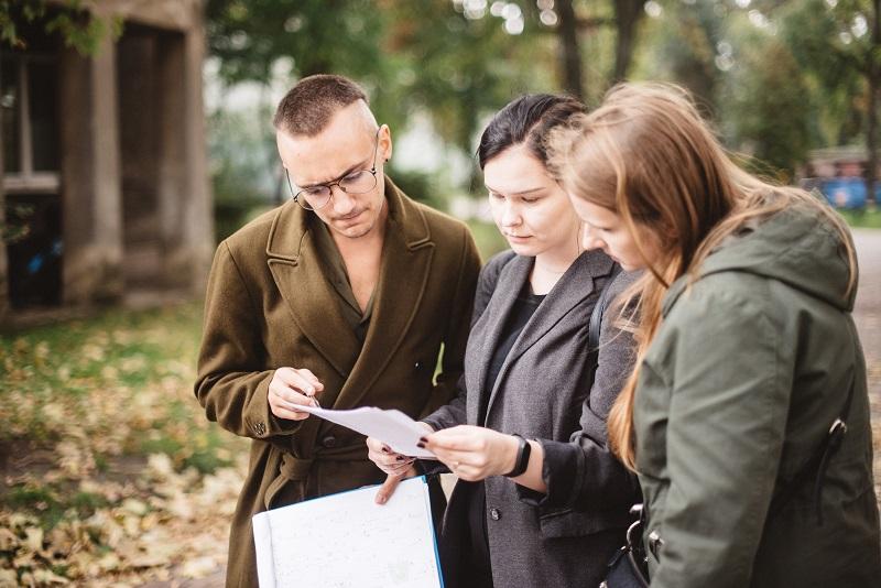 Trzy osoby stoją pochylone nad kartką.