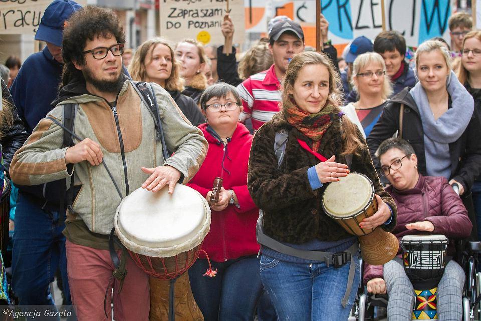 Zdjęcie z happeningu. Osoby uderzają w bębny, trzymają flagi i transparenty.