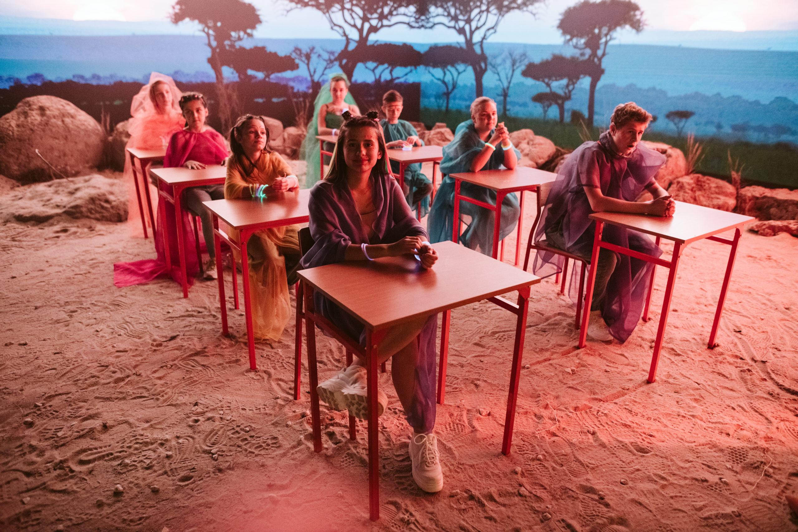 Plan zdjęciowy teledysku. Przy ławkach szkolnych siedzą dzieci, dookoła krajobraz sawanny w klimacie filmu