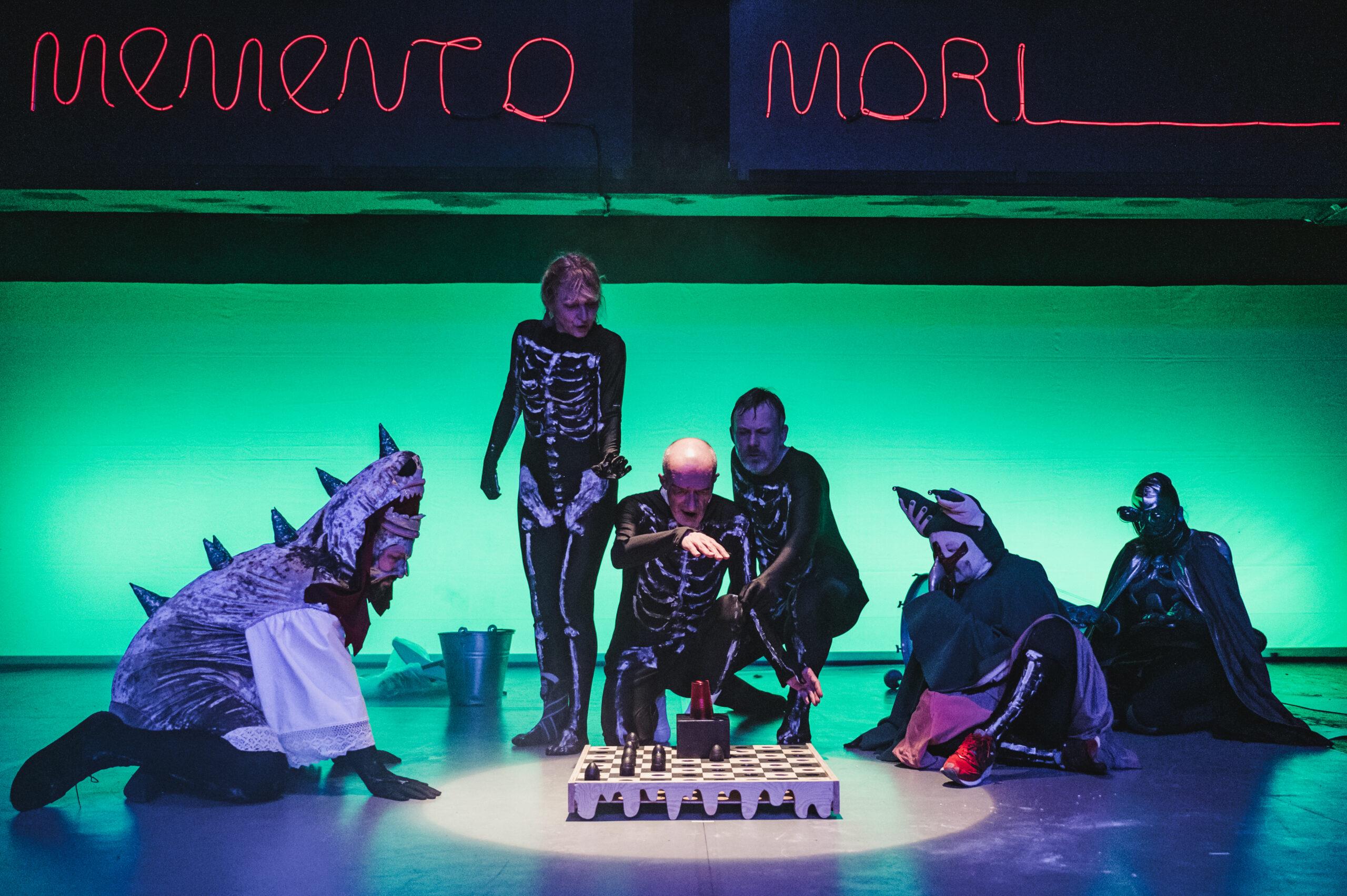 Zdjęcie ze spektaklu Gargantua i Pantagruel. Grupa osób przebranych za kościotrupy. Stoją przed dużą planszą do szachów. Nad nimi napis Memento mori.