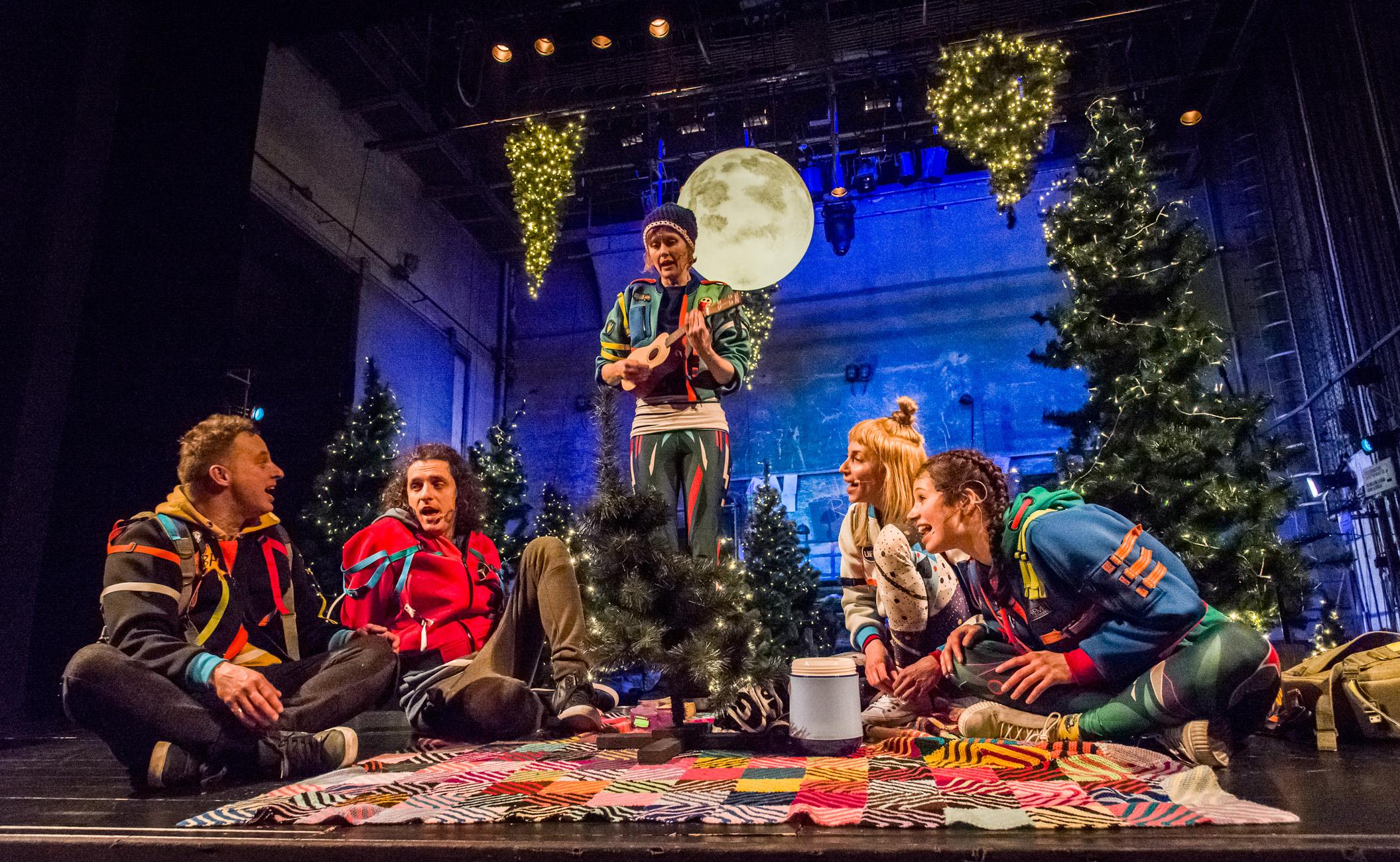 zdjęcie ze spektaklu. Dekoracje świąteczne. Na podłodze siedzą 4 osoby, a jedna wśród nich na środku stoi kobieta, trzyma w ręku małą gitarę i razem śpiewają.