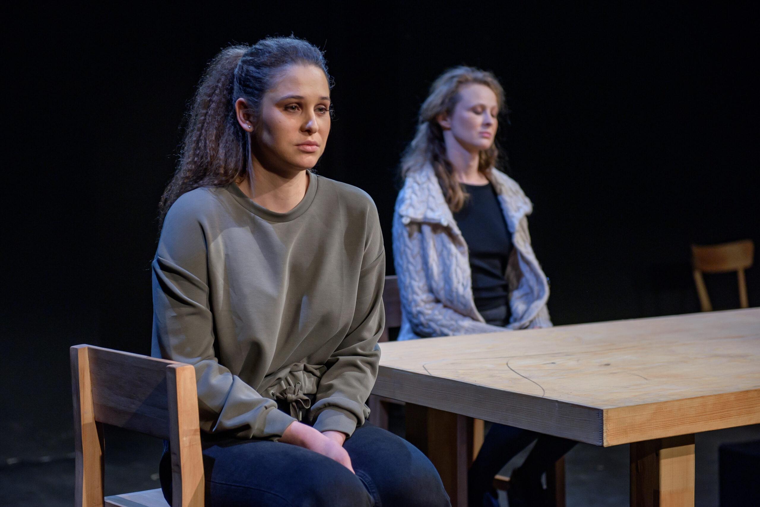 zdjęcie ze spektaklu. Przy dużym stole siedzą dwie kobiety, patrzą w tę samą stronę.