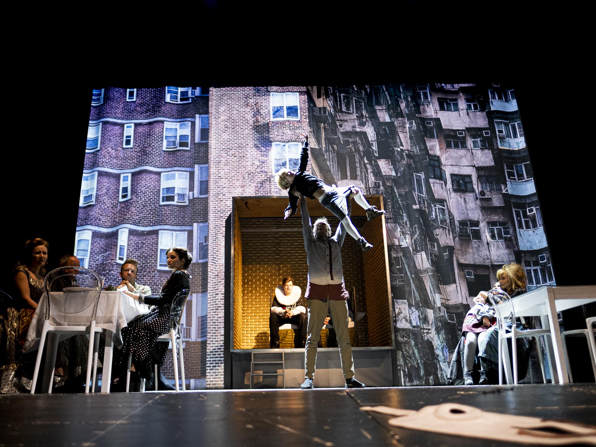 Zdjęcie ze spektaklu. Mężczyzna unosi dziecko, obok przy stolikach siedzą postaci.
