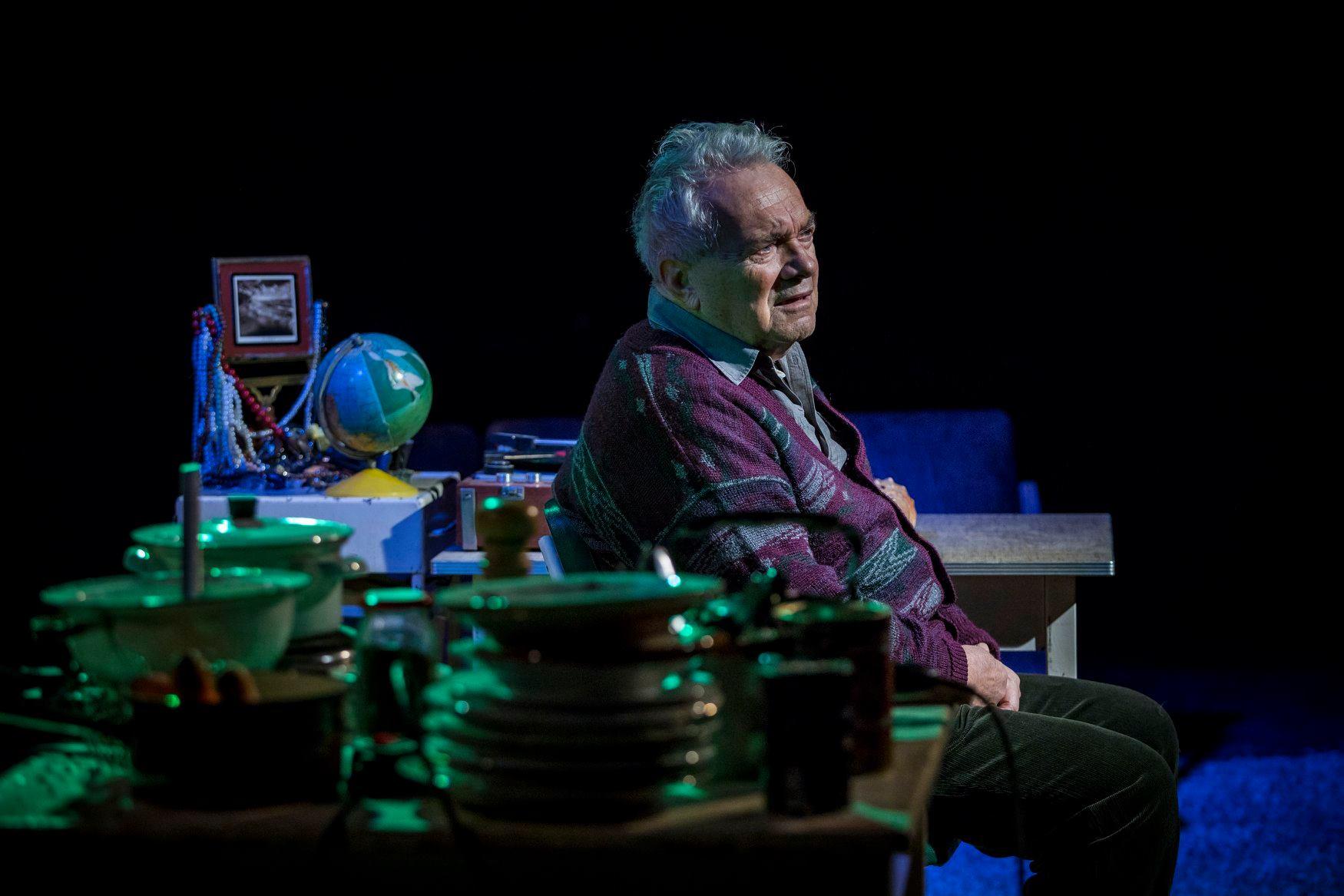 Zdjęcie ze spektaklu. Starszy mężczyzna siedzi na krześle, ma zmartwioną minę, dookoła bałagan.