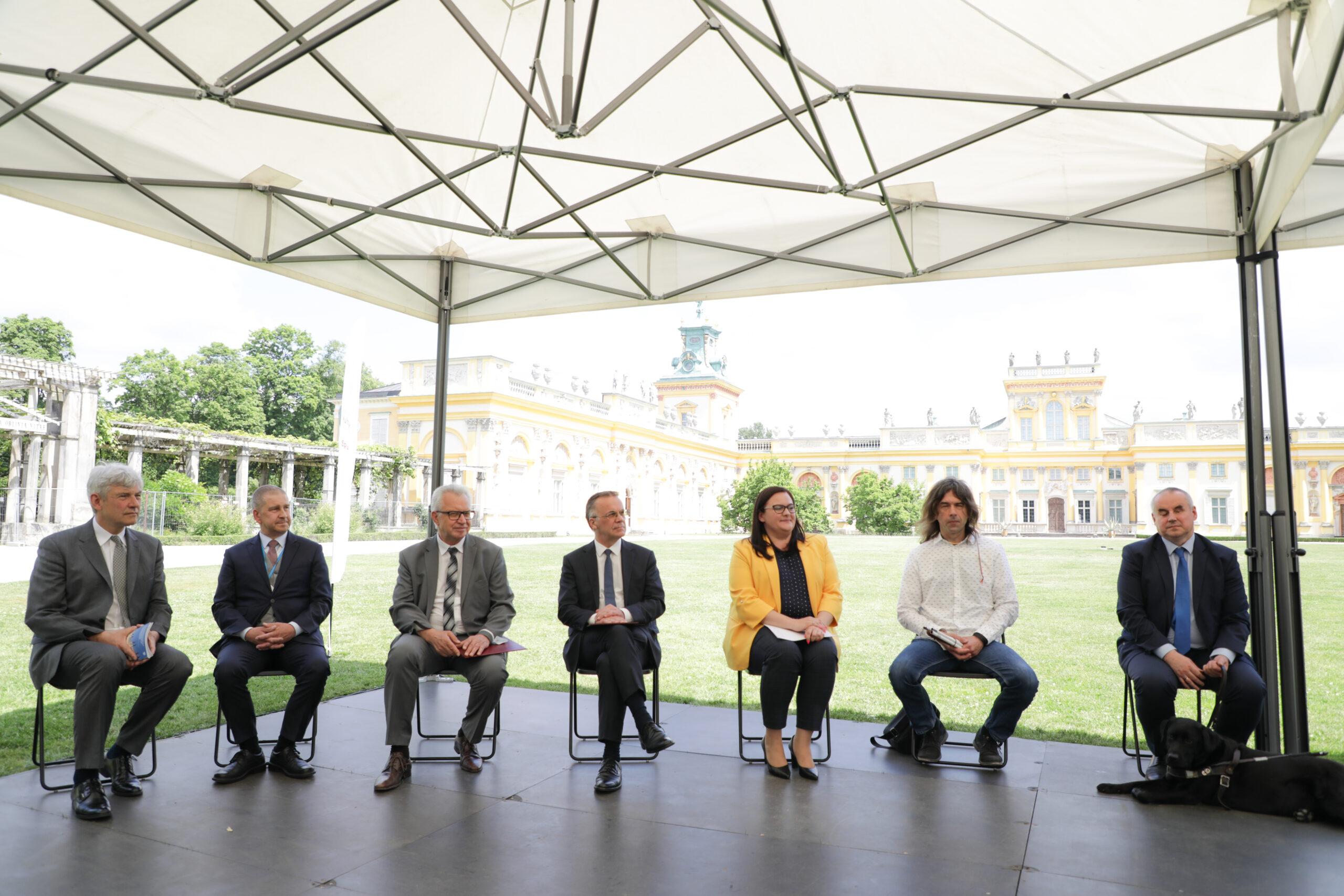 Zdjęcie z konferencji. Osoby reprezntujące projekt siedzą na krzesłach w rzędzie. Wśród nich Robert WIęckowski z FKBB.